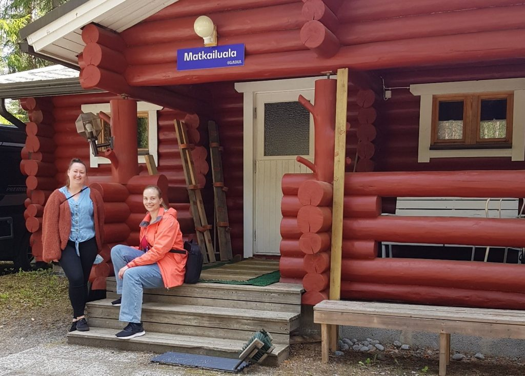 Julia ja Maaret matkailualan punaisen mökin edessä