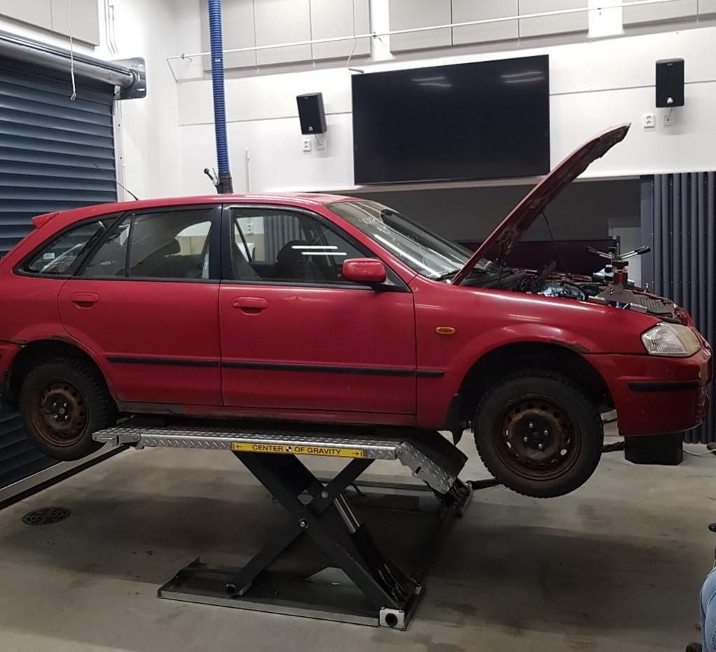Punainen auto korjattavana nostotelineellä autolabrassa