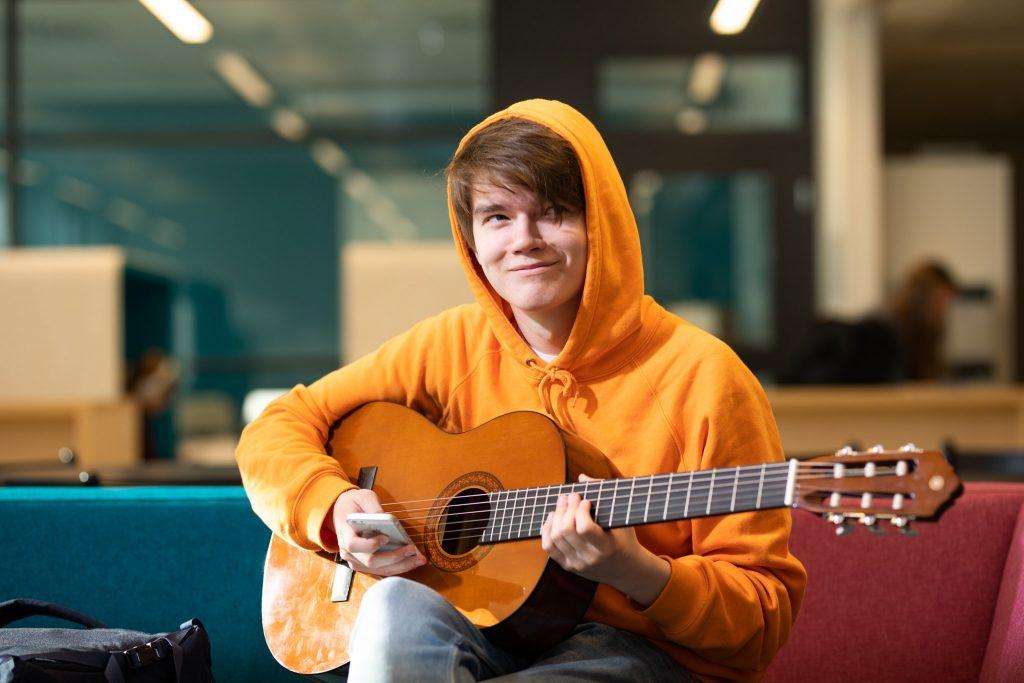 Gradian opiskelija soittaa kitaraa